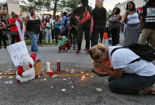 Meghan O'Donnell, 29, from St. Louis, prays at the spot where Michael Brown was killed Sunday evening, Aug. 10, 2014, in Ferguson, Mo. A few thousand people have crammed the street where a black man was shot multiple times by a suburban St. Louis police officer. The candlelight vigil Sunday night was for 18-year-old Michael Brown, who died a day earlier. Police say he was unarmed. (AP Photo/St. Louis Post-Dispatch, J.B. Forbes)  EDWARDSVILLE INTELLIGENCER OUT; THE ALTON TELEGRAPH OUT