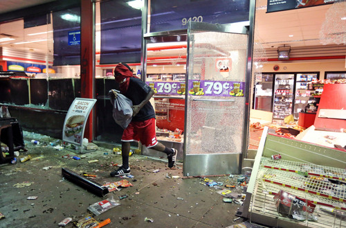 A man leaves a store on Sunday, Aug. 10, 2014, in Ferguson, Mo. A few thousand people crammed a suburban St. Louis street Sunday night at a vigil for unarmed 18-year-old Michael Brown who was shot and killed by a police officer, while afterward several car windows were smashed and stores were looted as people carried away armloads of goods as witnessed by an an Associated Press reporter. (AP Photo/St. Louis Post-Dispatch, David Carson)