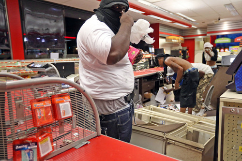 People are seen in a store Sunday, Aug. 10, 2014, in Ferguson, Mo. A few thousand people crammed a suburban St. Louis street Sunday night at a vigil for unarmed 18-year-old Michael Brown shot and killed by a police officer, while afterward several car windows were smashed and stores were looted as people carried away armloads of goods as witnessed by an an Associated Press reporter. (AP Photo/St. Louis Post-Dispatch, David Carson)