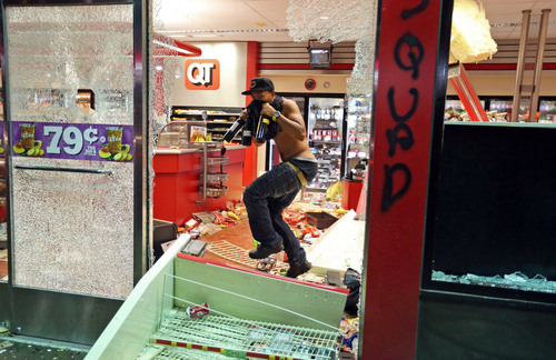 A man leaves a store on Sunday, Aug. 10, 2014, in Ferguson, Mo. A few thousand people crammed a suburban St. Louis street Sunday night at a vigil for unarmed 18-year-old Michael Brown shot and killed by a police officer, while afterward several car windows were smashed and stores were looted as people carried away armloads of goods as witnessed by an an Associated Press reporter. (AP Photo/St. Louis Post-Dispatch, David Carson)