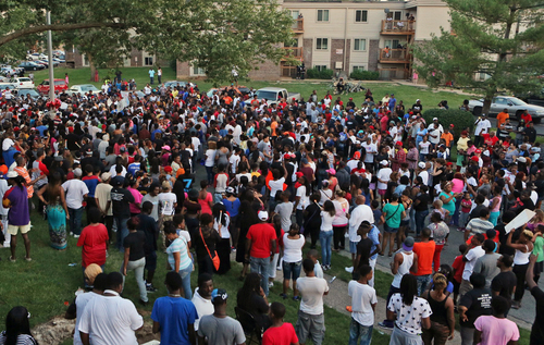 A large crowd gathers at the candlelight vigil, Sunday evening, Aug. 10, 2014, in Ferguson, Mo. A few thousand people have crammed the street where a black man was shot multiple times by a suburban St. Louis police officer. The candlelight vigil Sunday night was for 18-year-old Michael Brown, who died a day earlier. Police say he was unarmed. (AP Photo/St. Louis Post-Dispatch, J.B. Forbes)  EDWARDSVILLE INTELLIGENCER OUT; THE ALTON TELEGRAPH OUT