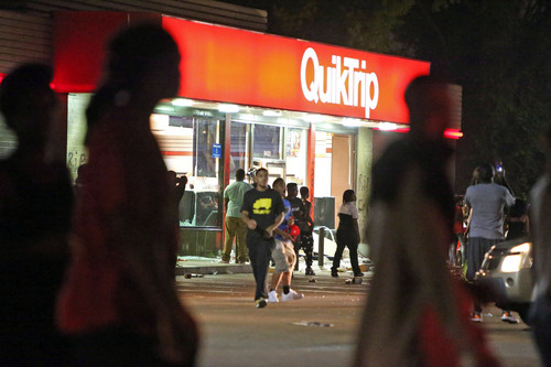 People are seen outside a store store Sunday, Aug. 10, 2014, in Ferguson, Mo. A few thousand people crammed a suburban St. Louis street Sunday night at a vigil for unarmed 18-year-old Michael Brown shot and killed by a police officer, while afterward several car windows were smashed and stores were looted as people carried away armloads of goods as witnessed by an an Associated Press reporter. (AP Photo/St. Louis Post-Dispatch, David Carson)