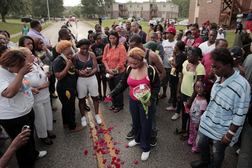 """Lesley McSpadden, center, drops rose petals on the blood stains from her 18-year-old son Michael Brown who was shot and killed by police in the middle of the street in Ferguson, Mo., near St. Louis on Saturday, Aug. 9, 2014. McSpadden, told an acquaintance the shooting was """"wrong and it was cold-hearted,"""" the St. Louis Post-Dispatch reported. A spokesman with the St. Louis County Police Department, which is investigating the shooting at the request of the local department, confirmed a Ferguson police officer shot the man. The spokesman didn't give the reason for the shooting. (AP Photo/St. Louis Post-Dispatch, Huy Mach)"""