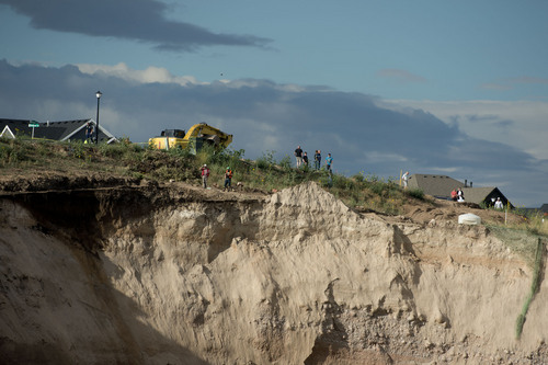Jeremy Harmon  |  The Salt Lake Tribune  People are seen at the top of an area damaged by a landslide in North Salt Lake on Tuesday, August 5, 2014. A home at the bottom of the slide was destroyed.