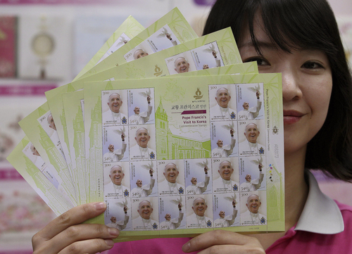 A worker at the Gwanghwamun Post Office unveils sheets of stamps to commemorate Pope Francis' visit to South Korea in Seoul, South Korea, Thursday, Aug. 7, 2014. Pope Francis is scheduled to make a five-day trip to South Korea, starting Aug. 14 to participate in a Catholic youth festival and to preside over a beatification ceremony for 124 Korean martyrs. (AP Photo/Ahn Young-joon)