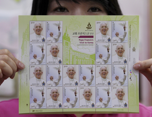 A worker at the Gwanghwamun Post Office shows a sheet of stamps to commemorate Pope Francis' visit to South Korea in Seoul, South Korea, Thursday, Aug. 7, 2014. Pope Francis is scheduled to make a five-day trip to South Korea, starting Aug. 14 to participate in a Catholic youth festival and to preside over a beatification ceremony for 124 Korean martyrs. (AP Photo/Ahn Young-joon)