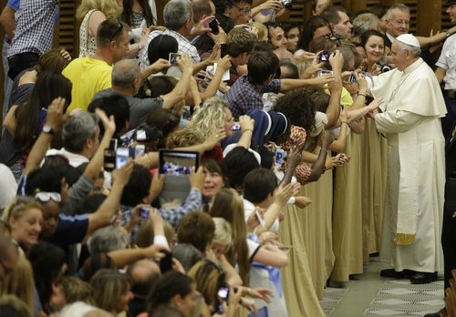 Pope Francis greets faithful at the end of his weekly general audience in the Paul VI hall, at the Vatican, Wednesday, Aug. 6, 2014. (AP Photo/Andrew Medichini)