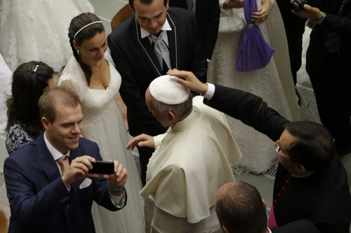 Pope Francis greets newly wed couples during the weekly general audience in the Paul VI hall, at the Vatican, Wednesday, Aug. 6, 2014. (AP Photo/Andrew Medichini)