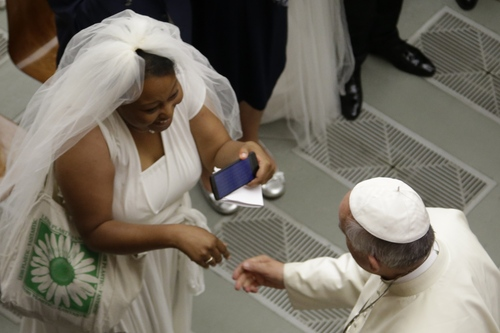Pope Francis greets a bride during the weekly general audience in the Paul VI hall, at the Vatican, Wednesday, Aug. 6, 2014. (AP Photo/Andrew Medichini)