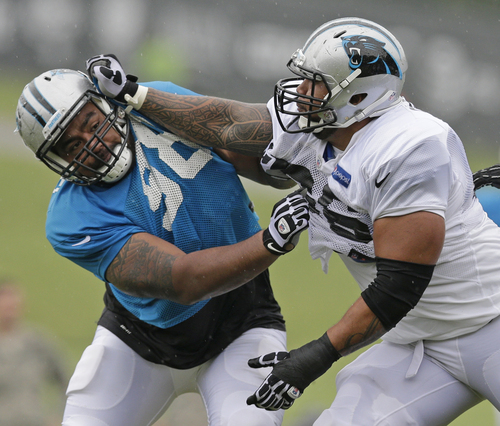 Carolina Panthers' Star Lotulelei, left, is blocked by Amini Silatolu, right, during an NFL football practice at their training camp in Spartanburg, S.C., Thursday, July 31, 2014. (AP Photo/Chuck Burton)