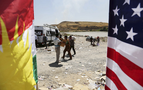 U.S. and Kurdish flags flutter in the wind as displaced Iraqis from the Yazidi community cross the Syria-Iraq border at Feeshkhabour bridge over the Tigris River at Feeshkhabour border point, in northern Iraq, Sunday, Aug. 10, 2014. Kurdish authorities at the border believe some 45,000 Yazidis passed the river crossing in the past week and  thousands more are still stranded in the mountains. (AP Photo/ Khalid Mohammed)