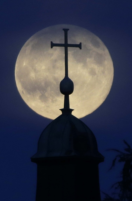 """The Supermoon appears behind a cross of the 'Christkoenig' church in Munich, southern Germany, Sunday, Aug. 10, 2014.  The phenomenon, which scientists call a """"perigee moon,"""" occurs when the moon is near the horizon and appears larger and brighter than other full moons. (AP Photo/Matthias Schrader)"""