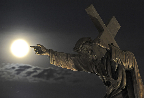 """A supermoon rises above a Jesus Christ statue in front of the Holy Cross church  in Warsaw, Poland, Sunday, Aug. 10, 2014. The phenomenon, which scientists call a """"perigee moon,"""" occurs when the moon is near the horizon and appears larger and brighter than other full moons.  (AP Photo/Alik Keplicz)"""