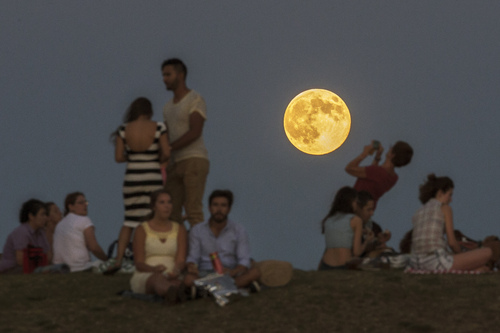 """People gather in the park as a perigee moon, also known as a supermoon, rises in Madrid, Sunday, Aug. 10, 2014. The phenomenon, which scientists call a """"perigee moon,"""" occurs when the moon is near the horizon and appears larger and brighter than other full moons. (AP Photo/Andres Kudacki)"""
