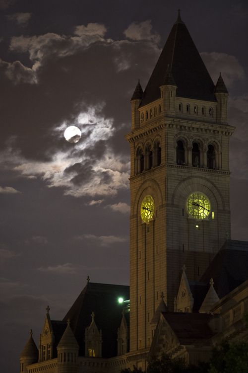 In this Sunday, Aug. 10, 2014 photo provided by NASA, a perigee full moon or supermoon is seen over the Old Post Office and Clock Tower, in Washington. (AP Photo/NASA, Bill Ingalls)