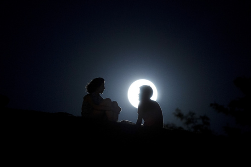 """A couple talk as they sit against  the perigee moon, also known as a supermoon, in Madrid, Sunday, Aug. 10, 2014. The phenomenon, which scientists call a """"perigee moon,"""" occurs when the moon is near the horizon and appears larger and brighter than other full moons. (AP Photo/Andres Kudacki)"""
