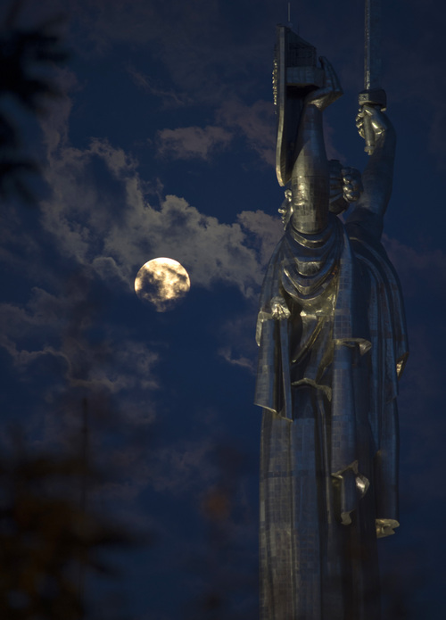 """The supermoon rises through the clouds behind the """"Motherland"""" statue, part of the WWII memorial complex, in Kiev, Ukraine, Sunday, Aug. 10, 2014. The phenomenon, which scientists call a """"perigee moon,"""" occurs when the moon is near the horizon and appears larger and brighter than other full moons. (AP Photo/Osman Karimov)"""