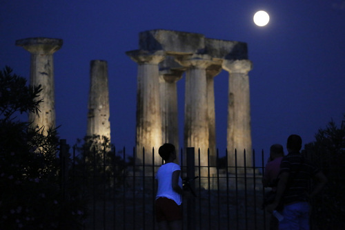 """People watch the super moon rising in the sky in front of the Apollo's temple at ancient Corinth about 80 kilometers (50 miles) southwest of Athens, on Sunday, Aug. 10, 2014. The phenomenon, which scientists call a """"perigee moon,"""" occurs when the moon is near the horizon and appears larger and brighter than other full moons. (AP Photo/Petros Giannakouris)"""