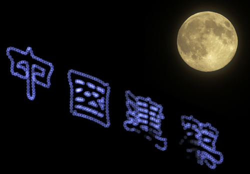 """The super moon rises over a Chinese words reads """"China construction"""" in Beijing, China Sunday, Aug. 10, 2014. The phenomenon, which scientists call a perigee moon, occurs when the moon is near the horizon and appears larger and brighter than other full moons. (AP Photo/Andy Wong)"""