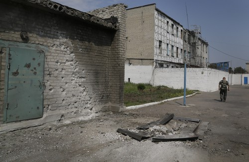 An officer walks outside a prison after shelling in Donetsk, eastern Ukraine, Monday, Aug. 11, 2014. Local authorities say more than 100 prisoners have fled from a high-security facility after it was hit by shelling in the rebel stronghold of Donetsk. City council spokesman Maxim Rovensky said Monday a jail riot was precipitated by a direct rocket hit that claimed the life of at least one inmate. The fugitives include people jailed for murder, robbery and rape. (AP Photo/Sergei Grits)