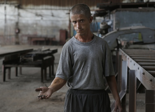 A prisoner displays fragments of a shell after shelling in Donetsk, eastern Ukraine, Monday, Aug. 11, 2014. Local authorities say more than 100 prisoners have fled from a high-security facility after it was hit by shelling in the rebel stronghold of Donetsk. City council spokesman Maxim Rovensky said Monday a jail riot was precipitated by a direct rocket hit that claimed the life of at least one inmate. The fugitives include people jailed for murder, robbery and rape. (AP Photo/Sergei Grits)