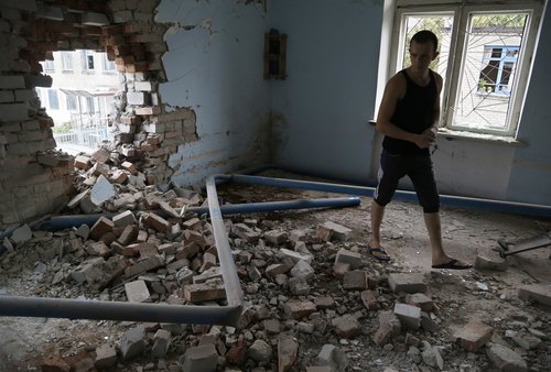 A prisoner inspects damage in a high-security facility after shelling in Donetsk, eastern Ukraine, Monday, Aug. 11, 2014. Local authorities say more than 100 prisoners have fled from a high-security facility after it was hit by shelling in the rebel stronghold of Donetsk. City council spokesman Maxim Rovensky said Monday a jail riot was precipitated by a direct rocket hit that claimed the life of at least one inmate. The fugitives include people jailed for murder, robbery and rape. (AP Photo/Sergei Grits)