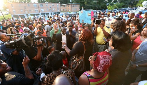 "Miah White, center with purse, leads the crowd in the choir song ""Break Every Chain"" during an impromptu rally on the front steps of the Murchison Tabernacle Church on Monday, Aug. 11, 2014, in Normandy, Mo.  The gathering at the church was in response to the police shooting of 18-year-old Michael Brown on Saturday. (AP Photo/St. Louis Post-Dispatch,  Chris Lee)  EDWARDSVILLE INTELLIGENCER OUT; THE ALTON TELEGRAPH OUT"