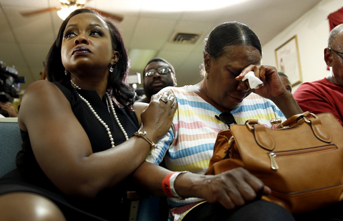 Phaedra Parks, left, comforts Desuirea Harris, the grandmother of Michael Brown, during a news conference Monday, Aug. 11, 2014, in Jennings, Mo. Michael Brown, 18, was shot and killed in a confrontation with police in the St. Louis suburb of Ferguson, Mo, on Saturday, Aug. 9, 2014.(AP Photo/Jeff Roberson)