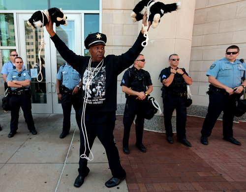 "Activist Anthony Shahid holds up two stuffed dogs which he wore around his neck during a rally across the Justice Center, Tuesday, Aug. 12, 2014, in Clayton, Mo., demanding justice for Michael Brown Jr. who was fatally shot by a Ferguson police officer last Saturday. Shahid said ""police have more respect for dogs than they do for black people."" (AP Photo/St. Louis Post-Dispatch, Laurie Skrivan)"