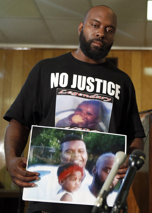 Michael Brown Sr., holds up a photo of himself, his son, Michael Brown, and a young child during a news conference Monday, Aug. 11, 2014, in Jennings, Mo. Michael Brown, 18, was shot and killed in a confrontation with police in the St. Louis suburb of Ferguson, Mo, on Saturday, Aug. 9, 2014.(AP Photo/Jeff Roberson)