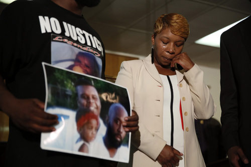Lesley McSpadden, the mother of 18-year-old Michael Brown, wipes away tears as Brown's father, Michael Brown Sr., holds up a family picture of himself, his son, top left, and a young child during a news conference Monday, Aug. 11, 2014, in Jennings, Mo. Michael Brown, 18, was shot and killed in a confrontation with police in the St. Louis suburb of Ferguson, Mo, on Saturday, Aug. 9, 2014.(AP Photo/Jeff Roberson)