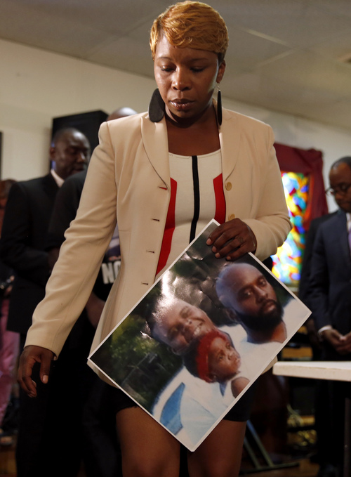 Lesley McSpadden, the mother of 18-year-old Michael Brown, holds a photo of her son, seen at top left, as she attends a news conference Monday, Aug. 11, 2014, in Jennings, Mo. Michael Brown was shot and killed in a confrontation with police in the St. Louis suburb of Ferguson, Mo, on Saturday, Aug. 9, 2014.(AP Photo/Jeff Roberson)
