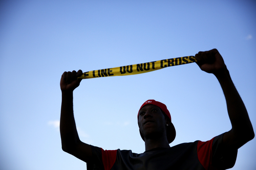 A man holds up a piece of police tape during a protest Monday, Aug. 11, 2014, in Ferguson, Mo. The FBI opened an investigation Monday into the death of 18-year-old Michael Brown, who police said was shot multiple times Saturday after being confronted by an officer in Ferguson. (AP Photo/Jeff Roberson)