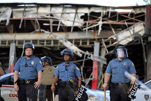 Police wearing riot gear stage outside the remains of a burned convenience store Monday, Aug. 11, 2014, in Ferguson, Mo. The FBI opened an investigation Monday into the death of 18-year-old Michael Brown, who police said was shot multiple times Saturday after being confronted by an officer in Ferguson. Authorities in Ferguson used tear gas and rubber bullets to try to disperse a large crowd Monday night that had gathered at the site of a burned-out convenience store damaged a night earlier, when many businesses in the area were looted. (AP Photo/Jeff Roberson)