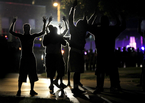 People raise their hands in the middle of the street as police wearing riot gear move toward their position trying to get them to disperse Monday, Aug. 11, 2014, in Ferguson, Mo. The FBI opened an investigation Monday into the death of 18-year-old Michael Brown, who police said was shot multiple times Saturday after being confronted by an officer in Ferguson. Authorities in Ferguson used tear gas and rubber bullets to try to disperse a large crowd Monday night that had gathered at the site of a burned-out convenience store damaged a night earlier, when many businesses in the area were looted. (AP Photo/Jeff Roberson)