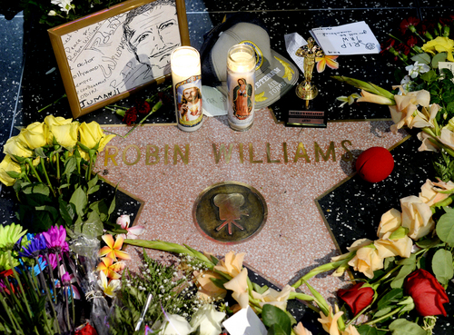"""Flowers are placed in memory of actor/comedian Robin Williams on his Walk of Fame star in the Hollywood district of Los Angeles, Monday, Aug. 11, 2014. Williams, a brilliant shapeshifter who could channel his frenetic energy into delightful comic characters like """"Mrs. Doubtfire"""" or harness it into richly nuanced work like his Oscar-winning turn in """"Good Will Hunting,"""" died Monday in an apparent suicide. He was 63. Williams was pronounced dead at his San Francisco Bay Area home Monday, according to the sheriff's office in Marin County, north of San Francisco. (AP Photo/Kevork Djansezian)"""
