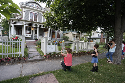 A woman takes a picture with her phone as others pay their respects at the home where the 80s TV series Mork & Mindy, starring the late Robin Williams, was set, in Boulder, Colo., Monday Aug. 11, 2014. Robin Williams, the Academy Award winner and comic supernova whose explosions of pop culture riffs and impressions dazzled audiences for decades and made him a gleamy-eyed laureate for the Information Age, died Monday in an apparent suicide. He was 63. (AP Photo/Brennan Linsley)