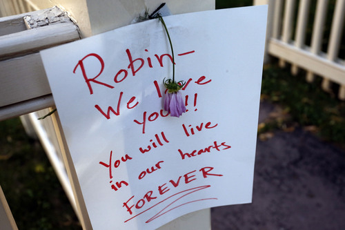 A sign and a flower are affixed to the front gate at a makeshift memorial outside the home where the 80s TV series Mork & Mindy, starring the late Robin Williams, was set, in Boulder, Colo., Tuesday Aug. 12, 2014. Williams, the Academy Award winner and comic supernova whose explosions of pop culture riffs and impressions dazzled audiences for decades and made him a gleamy-eyed laureate for the Information Age, died Monday, Aug. 11 in an apparent suicide. He was 63. (AP Photo/Brennan Linsley)