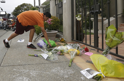 Brandon Antonio, 13, of San Rafael, leaves flowers outside of the home of Robin Williams in Tiburon, Calif., Tuesday, Aug. 12, 2014. Williams died Monday in an apparent suicide at his San Francisco Bay Area home, according to the sheriff's office in Marin County, north of San Francisco. (AP Photo/Jeff Chiu)