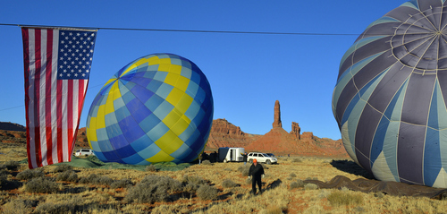 Keith Johnson | The Salt Lake Tribune  An American flag is tethered to the hot air balloon Midnight Blue, right, while crew members prepare to launch it and the balloon Locopelli, left, in the Valley of the Gods in Southeastern Utah on the last day of the16th annual Bluff Balloon Festival outside Bluff, Utah January 19, 2014.