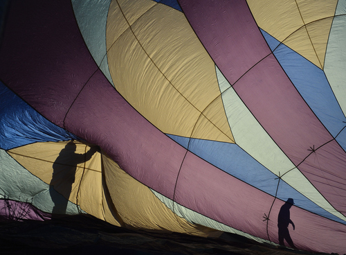 Keith Johnson | The Salt Lake Tribune  Midnight Blue crew members prepare to launch their hot air balloon in the Valley of the Gods in Southeastern Utah on the last day of the16th annual Bluff Balloon Festival outside Bluff, Utah January 19, 2014.