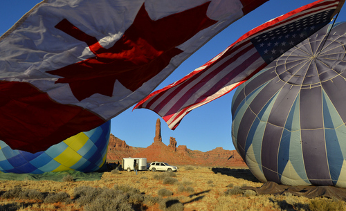 Keith Johnson | The Salt Lake Tribune  Canadian and American flags fly from the hot air balloon Midnight Blue, right, while crew members prepare to launch it and the balloon Locopelli, left, in the Valley of the Gods in Southeastern Utah on the last day of the16th annual Bluff Balloon Festival outside Bluff, Utah January 19, 2014.