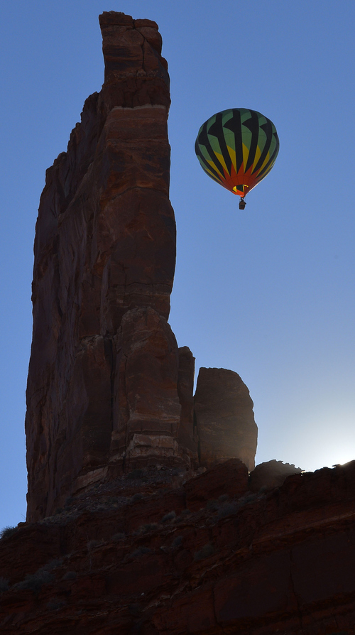 Keith Johnson | The Salt Lake Tribune  A hot air balloon flies past a rock spire in the Valley of the Gods in Southeastern Utah on the last day of the16th annual Bluff Balloon Festival outside Bluff, Utah January 19, 2014.