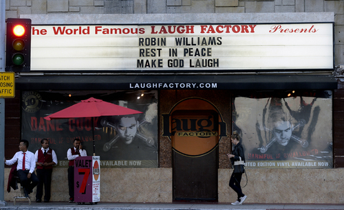 A person walks past the marquee of the Laugh Factory with a message in memory of actor/comedian Robin Williams in the Hollywood district of Los Angeles, Monday, Aug. 11, 2014. Williams, the Academy Award winner and comic supernova whose explosions of pop culture riffs and impressions dazzled audiences for decades and made him a gleamy-eyed laureate for the Information Age, died Monday in an apparent suicide at his San Francisco Bay area home. He was 63. (AP Photo/Kevork Djansezian)