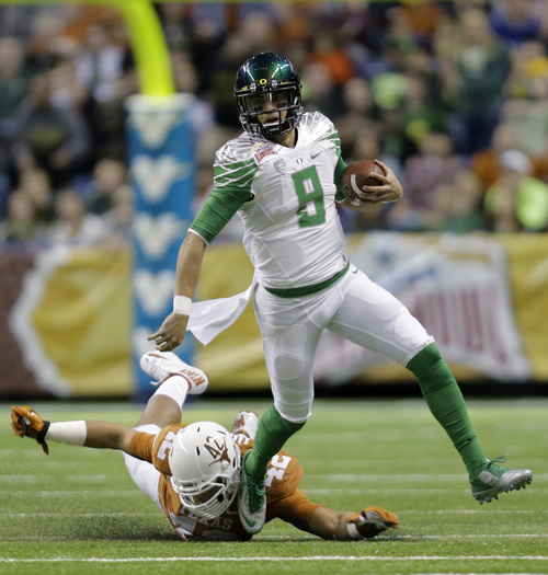 FILE - In this Dec. 30, 2013, file photo, Oregon's Marcus Mariota (8) is pursued by Texas' Caleb Bluiett (42) during the first quarter in the Valero Alamo Bowl NCAA college football game in San Antonio. If he stays healthy, Mariota is one of the nation's best dual-threat quarterbacks and could find himself holding that bronze trophy. (AP Photo/Eric Gay, File)