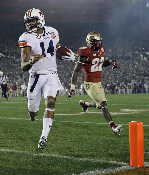 FILE - In this Jan. 6, 2014, file photo, Auburn's Nick Marshall (14) gets past Florida State's Telvin Smith (22) for a touchdown run during the first half of the NCAA BCS National Championship college football game in Pasadena, Calif. Marshall is expected to have another big season after passing for 1,976 yards, running for 1,068 and accounting for 26 touchdowns while leading the Tigers to the final BCS national championship game last year. (AP Photo/David J. Phillip, File)