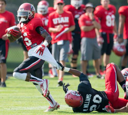 Al Hartmann  |  The Salt Lake Tribune  Wide receiver Kenneth Scott, right, makes a long pass grab defended by defensive back Davion Orphey during practice at Ute football camp Wednesday August 13, 2014.