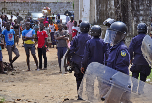 Liberian policemen, right, dressed in riot gear disperse a crowd of people that blocked a main road after the body of someone suspected of dying from the Ebola virus was not removed by health workers in the city of  Monrovia, Liberia.  Thursday, Aug. 14, 2014. Liberia faced an excruciating choice Thursday: deciding which handful of Ebola patients will receive an experimental drug that could prove either life-saving or life-threatening. ZMapp, the untested Ebola drug, arrived in the West African country late Wednesday. Assistant Health Minister Tolbert Nyenswah said three or four people would begin getting it Thursday. The government had previously said two doctors would receive the treatment, but it was unclear who else would. These are the last known doses of ZMapp left in the world. The San Diego-based company that developed it has said it will take months to build up even a modest supply. (AP Photo/Abbas Dulleh)