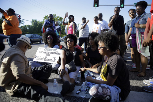 A small group of protesters block traffic by sitting in the street before police in riot gear arrived in Ferguson, Mo. on Wednesday, Aug. 13, 2014. On Saturday, Aug. 9, 2014, a white police officer fatally shot Michael Brown, an unarmed black teenager in the St. Louis suburb. (AP Photo/Jeff Roberson)