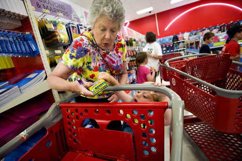 FILE - In this July 23, 2014 file photo, Julie Wilkins helps her grandson, Griffin Brady, 3, put a box of crayons in a shopping cart while shopping for school supplies with her family at a Target store in Memphis, Tenn. The National Retail Federation, the nation's largest retail industry trade organization, expects the average family with children from kindergarten through grade 12 will spend $669.28 on clothing, shoes, supplies and electronics for the back-to-school season, up 5 percent from $634.78 last year. (AP Photo/The Commercial Appeal, Brandon Dill, File)
